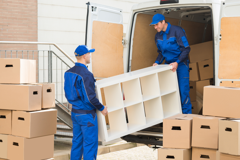 Young,Male,Movers,Unloading,Furniture,And,Cardboard,Boxes,From,Truck